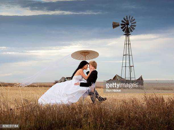 A bride and groom in a farm field
