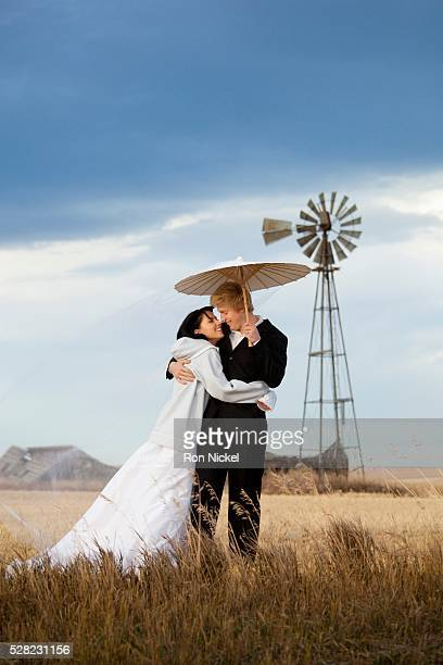 A bride and groom in an embrace in a farm field