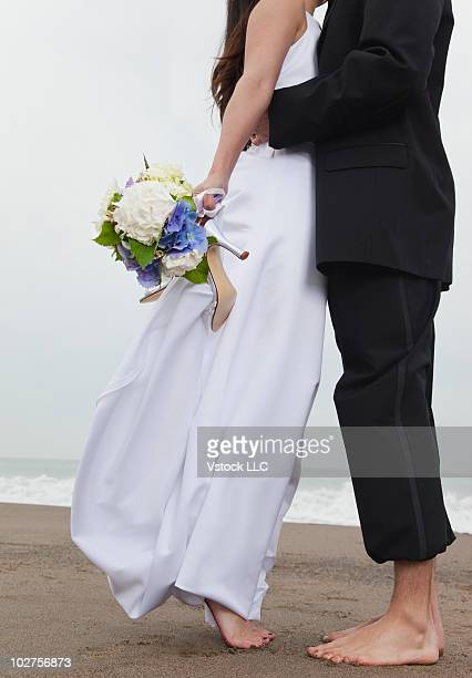 Bride and groom in bare feet at the beach