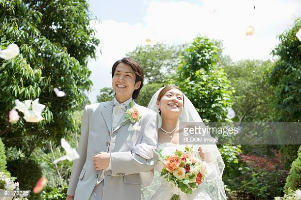 Bride and groom in flower shower, smiling, walking arm in arm