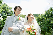 Bride and groom in flower shower, smiling, walking arm in arm