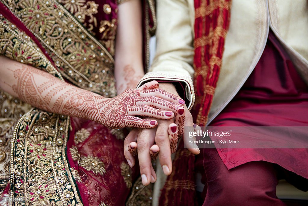 Bride And Groom In Traditional Indian Wedding Clothing With Henna