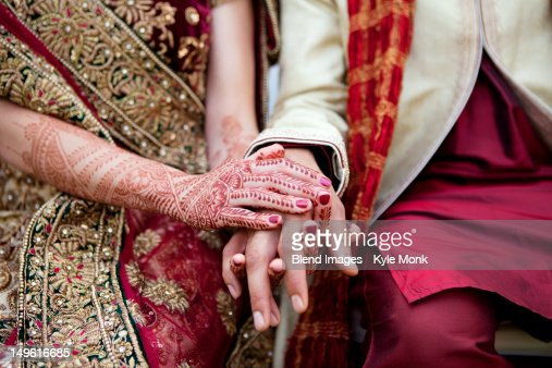 Bride and groom in traditional Indian wedding clothing with henna tattoos : Stock Photo