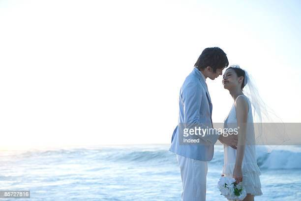 Bride and groom kissing at beach