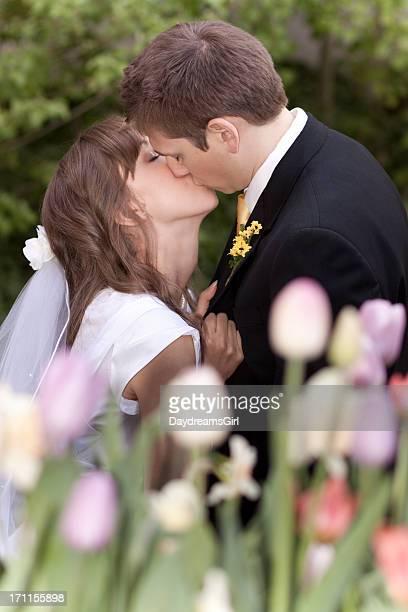 Mariée et le marié Embrasser derrière le jardin fleuri