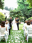 Bride and groom kissing during outdoor wedding ceremony