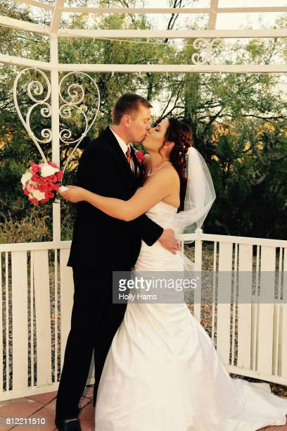 Bride and groom kissing in a gazebo at wedding