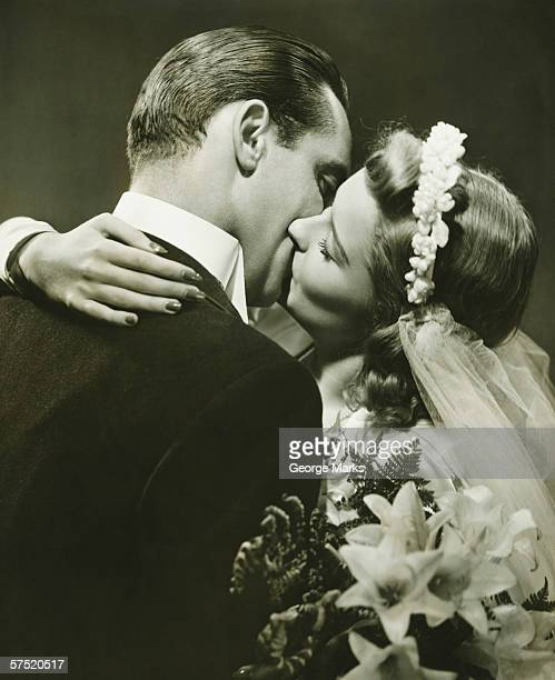 Bride and Groom kissing in studio, (B&W)