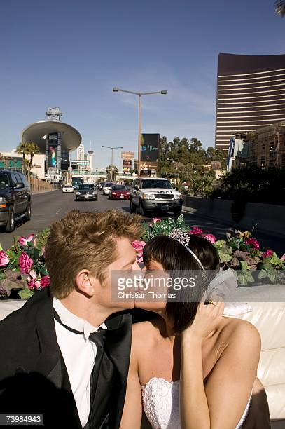 Bride and groom kissing in the back seat of a convertible car