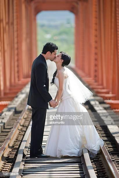 Bride and Groom Kissing on Railroad Track Bridge