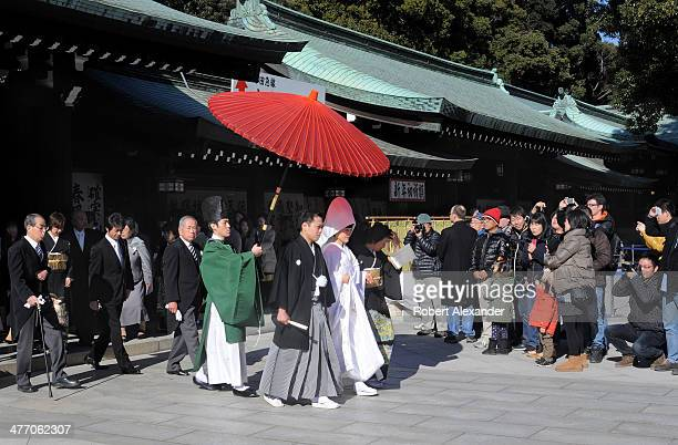 A bride and groom leads their wedding entourage at a Shinto wedding at the MeijiJingu shrine in the Harajuku district of Tokyo The couple walks under...