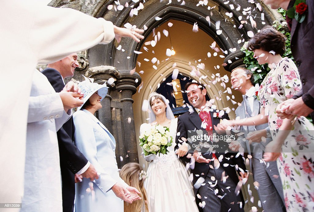 Bride and groom leaving church showerd in flower petals by guests : Stock Photo