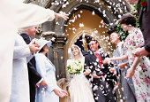 Bride and groom leaving church showerd in flower petals by guests