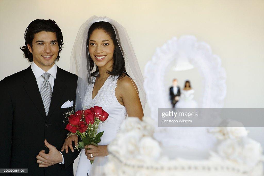 Bride and groom near wedding cake, portrait : Stock Photo
