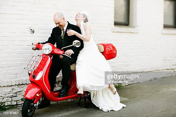 Bride and groom on red motorbike