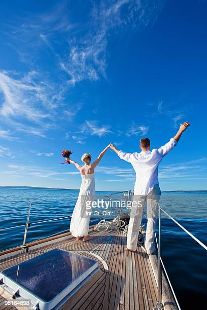 Bride and groom on sailboat looking out, arms up