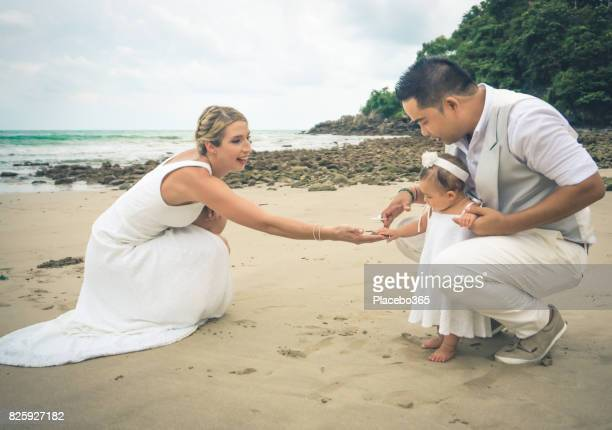 Bride and Groom on the beach with Baby Daughter