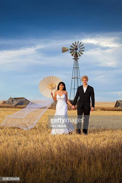 A bride and groom posing in a farm field