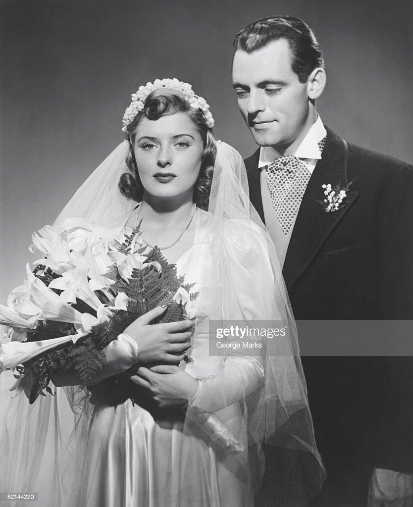 Bride and groom posing in studio, (B&W), portrait : Stock Photo