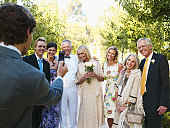 Bride and groom posing with wedding guests for camera phone