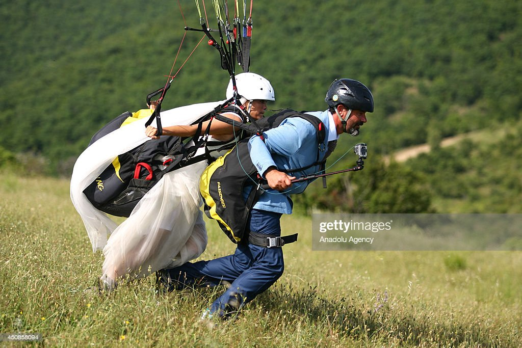 Bride and groom prepare for paragliding in Sarkoy district of Tekirdag, Turkey on June 19, 2014. Kivanc Altun and Nilufer Altun are a married couple who met while paragliding in Sarkoy came to same place after their wedding to paraglide with their wedding dresses on.