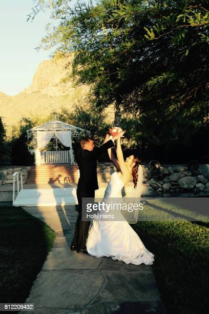 Bride and groom raising arms together playfully, facing each other