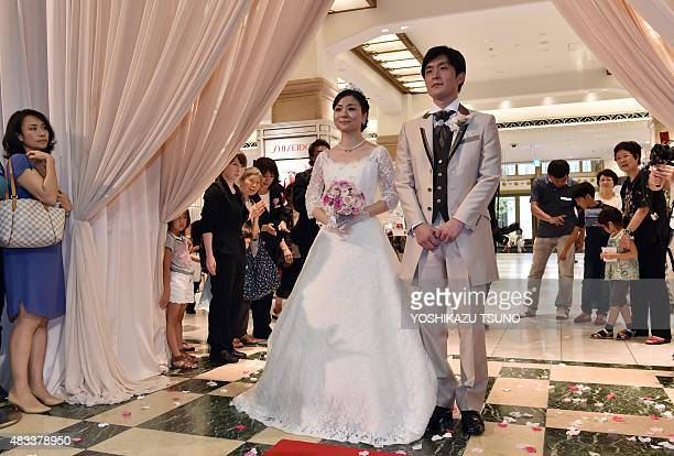 Bride and groom Rie Oka and Kazuya Fukushima attend their wedding ceremony at the Mitsukoshi department store in Tokyo on August 8 2015 Mitsukoshi...