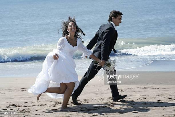 Le marié et la mariée courir sur la plage