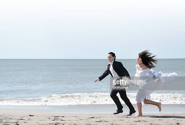 Bride and groom running at the beach