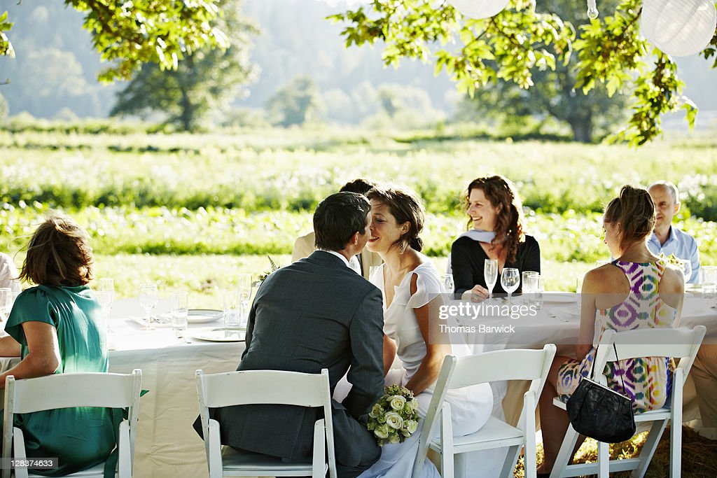 Bride and groom seated at table about to kiss : Stock Photo