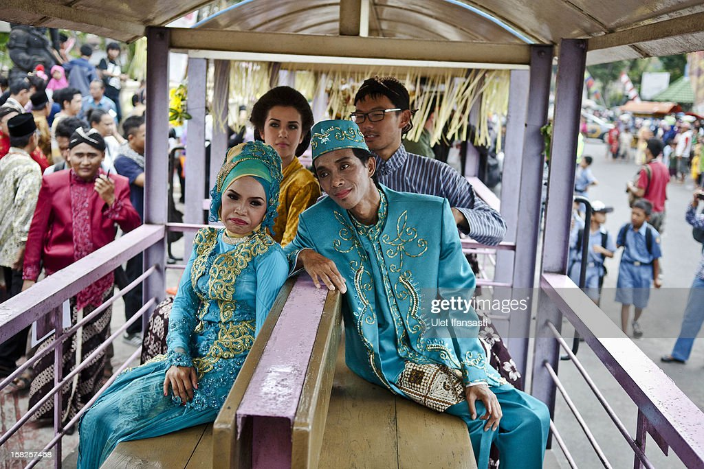 A bride and groom sit inside a lorry train parade during a mass wedding ceremony on December 12, 2012 in Yogyakarta, Indonesia. Twelve couples participated in a mass wedding as today saw a surge in marriage across the globe to mark the once in a century date of 12/12/12.
