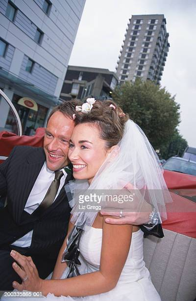 Bride and groom sitting in convertible car in street, smiling