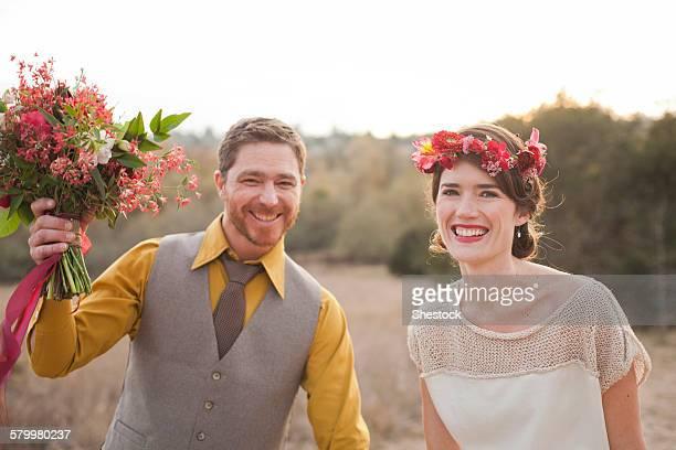 Bride and groom smiling in rural field