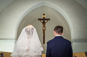 Photo taken during the wedding ceremony in Catholic church. Groom and bride stand before crucifix. Focus is on the crucifix. Newlyweds are in focus. Bride dressed in wedding dress and bridal veil. Gro