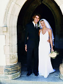 Bride and Groom Stand Side-by-Side at the Door of a Church