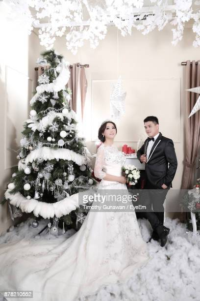 Bride And Groom Standing Against Christmas Tree At Home