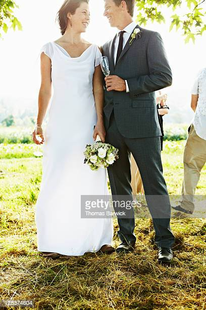 Bride and groom standing in field smiling