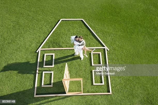 Bride and groom standing inside house outline