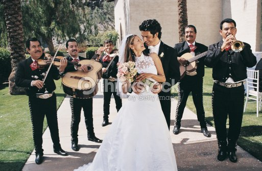 Bride And Groom Standing With A Mariachi Band In A Church Garden Stock Photo