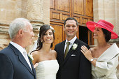 Bride and groom standing with parents, smiling