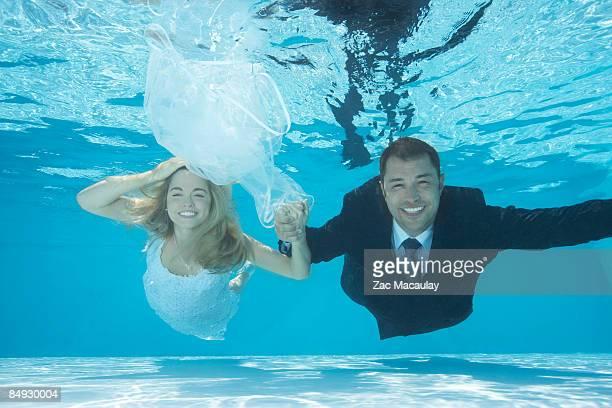 Bride and groom swimming underwater