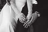 Bride and groom tenderly hold each other's hands. BW tone