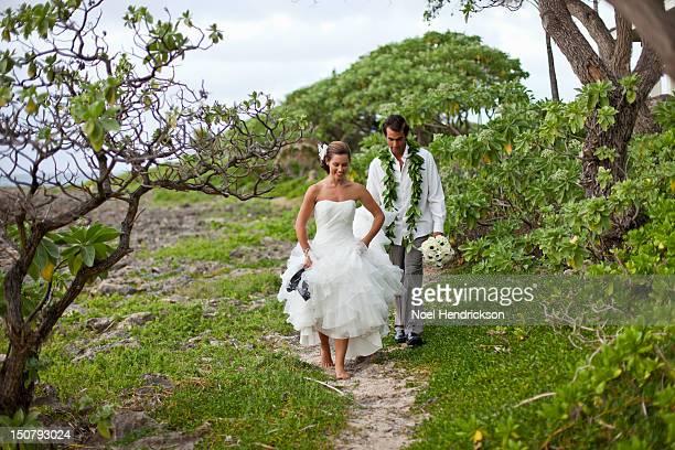 A bride and groom walk on their beach wedding day
