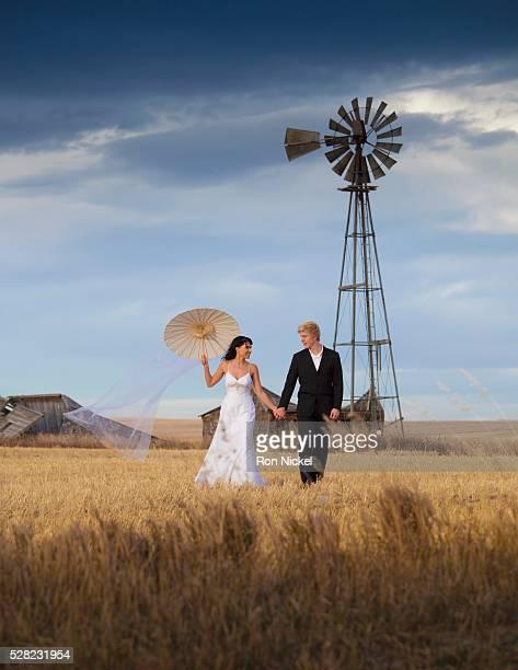 A bride and groom walking across farm land