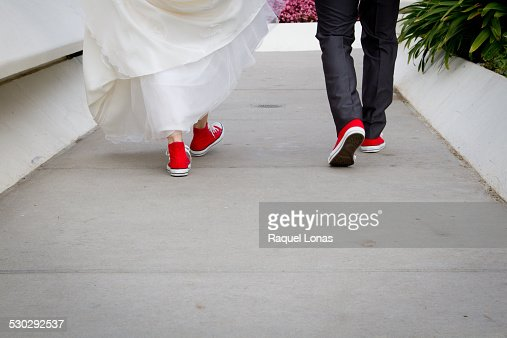 Bride and groom walking away in red sneakers
