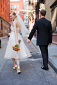 Bride and groom walking hand in hand on cobblestone street, bride looking back, New York City, NY