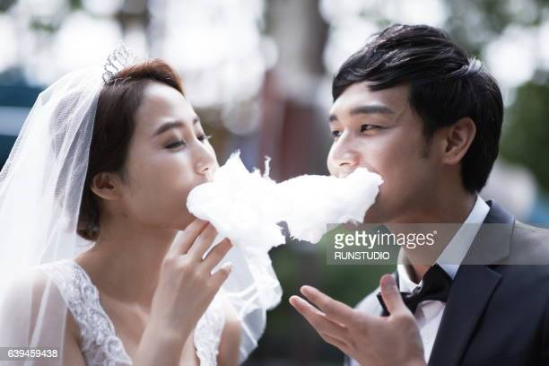 Bride and groom walking in the park with cotton candy