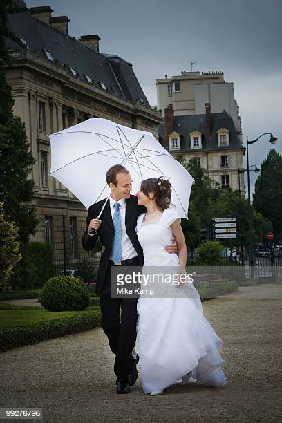 Bride and groom walking in the rain