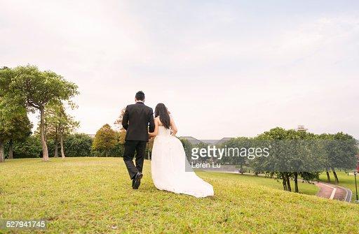 Bride and groom walking on meadow