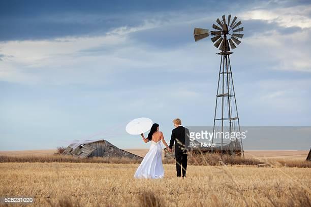 A bride and groom walking through a farm field